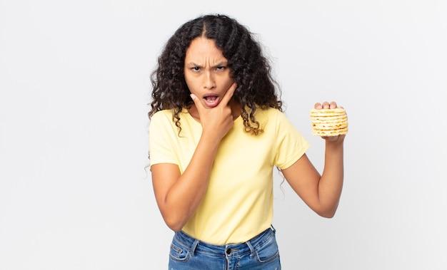 Jolie femme hispanique tenant des gâteaux de régime de riz