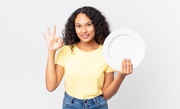 Jolie femme hispanique tenant un plat propre vide