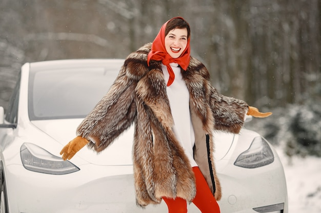Jolie femme en hiver en plein air avec une voiture blanche