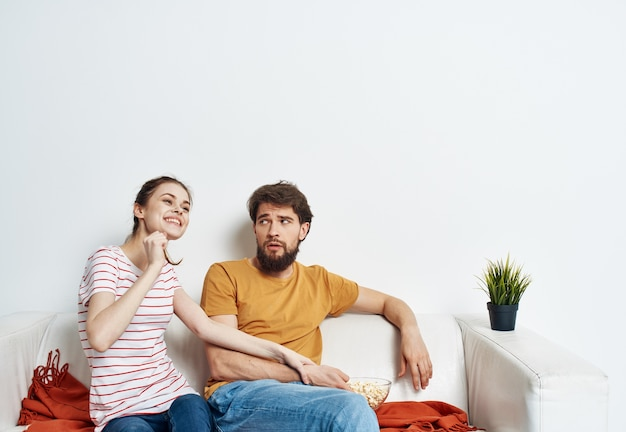 Jolie femme et homme sur canapé à carreaux orange et fleur en pot love family