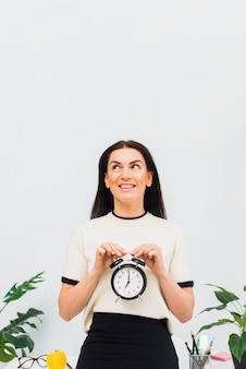 Jolie femme avec horloge dans les mains en souriant