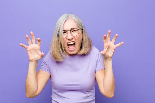 Jolie femme hurlant de panique ou de colère, choquée, terrifiée ou furieuse, les mains près de la tête