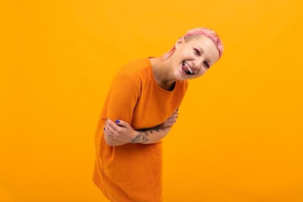Jolie femme inhabituelle aux cheveux roses courts et sourires de tatouage isolé sur orange