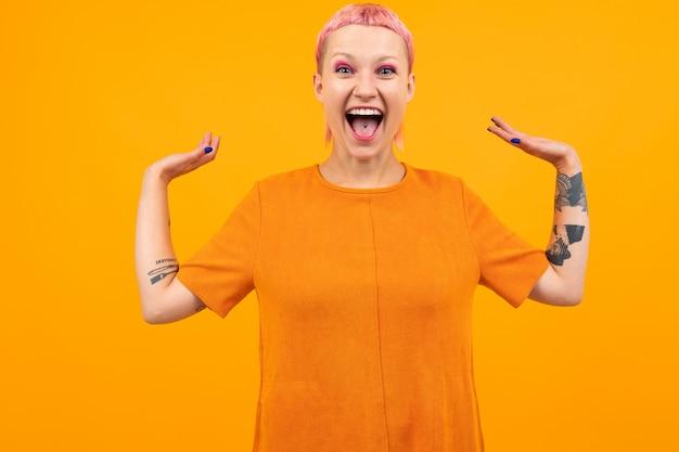 Jolie femme inhabituelle aux cheveux roses courts et tatouage crie de bonheur isolé sur orange