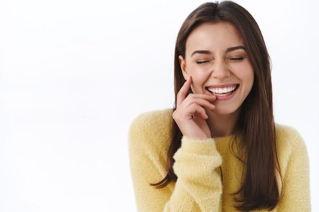 Jolie femme insouciante riant bêtement avec les yeux fermés et le vrai sourire, touche doucement la joue comme s'amusant, rigole sur une blague hilarante, mur blanc