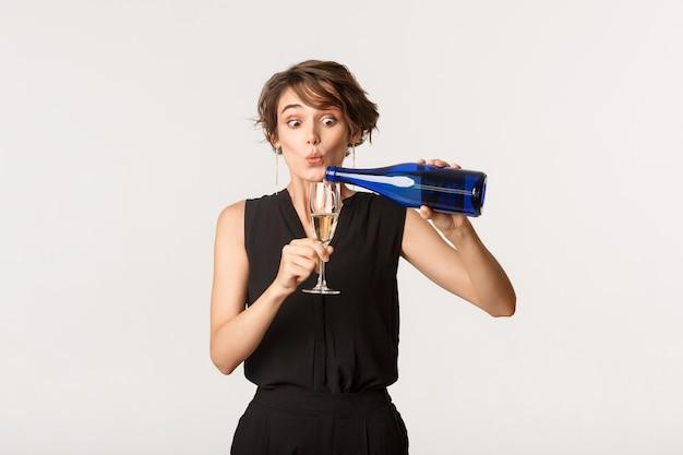 Jolie femme ivre versant du champagne dans son verre, debout sur blanc.