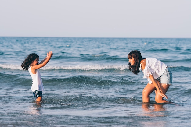 Jolie femme avec un jean bleu court et sa fille jouant dans l'eau de la plage