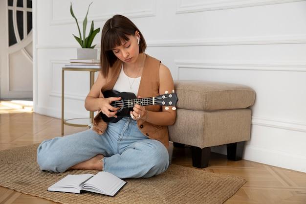Jolie femme jouant du ukulélé à la maison