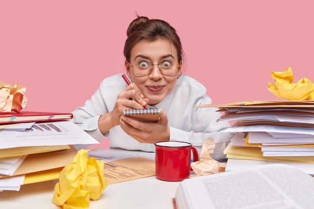 Jolie femme joyeuse écrit la liste des choses dans le bloc-notes, tient un stylo, porte de grandes lunettes optiques, a les cheveux noirs peignés en noeud, pose sur le lieu de travail avec des documents