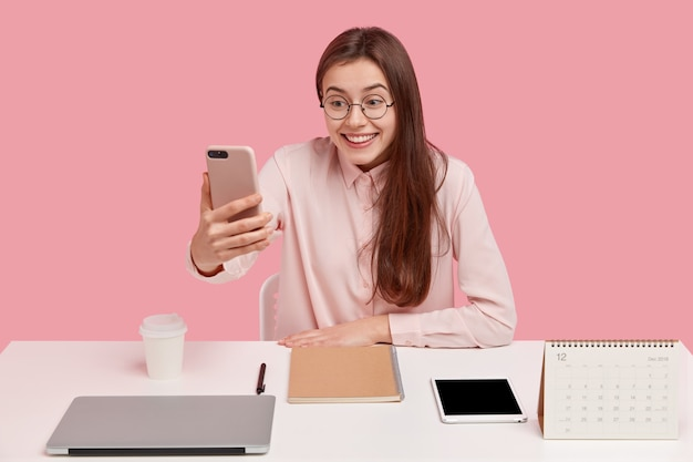 Jolie femme joyeuse avec un sourire agréable, tient le téléphone mobile devant le visage, vêtue d'une chemise élégante, fait un appel vidéo, heureux de remarquer un ami à distance