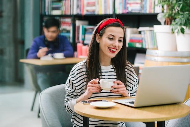 Jolie femme joyeuse tenant une tasse alors qu'elle était assise dans un café et regardant l'écran de l'ordinateur portable