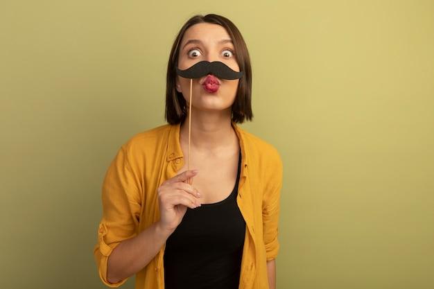 Jolie femme joyeuse tient une fausse moustache sur bâton isolé sur un mur vert olive