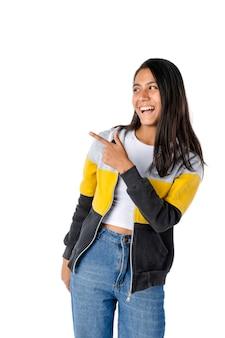 Jolie femme latina aux cheveux noirs et droite pointant sur le côté avec un grand sourire regardant dans le même espace pointu