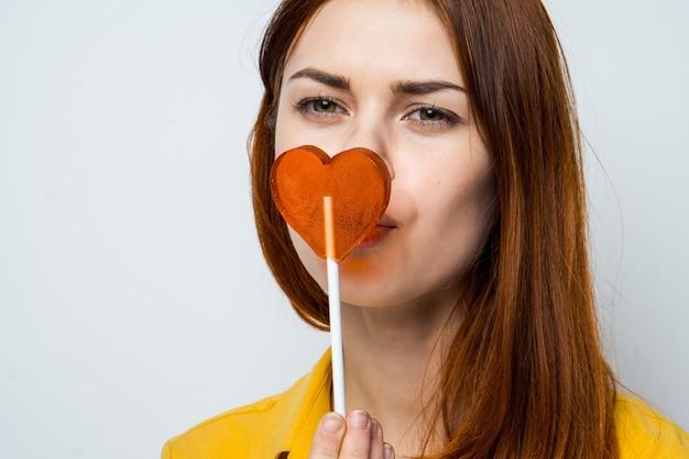 Jolie femme léchant le studio de gros plan sucette coeur. photo de haute qualité