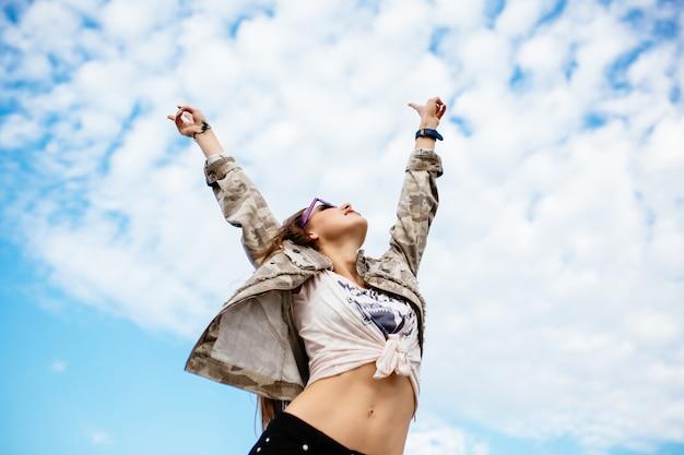 Jolie femme leva les mains, profitant d'une journée parfaite, la liberté