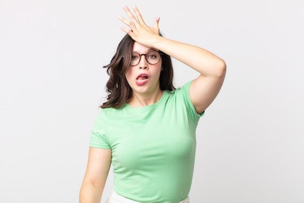 Jolie femme levant la paume vers le front pensant oops, après avoir fait une erreur stupide ou s'être souvenue, se sentir stupide