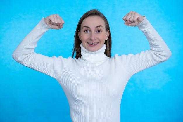 Une jolie femme lève les bras et montre que les biceps démontrent que les muscles sont fiers de leurs réalisations personnelles sur un mur bleu.