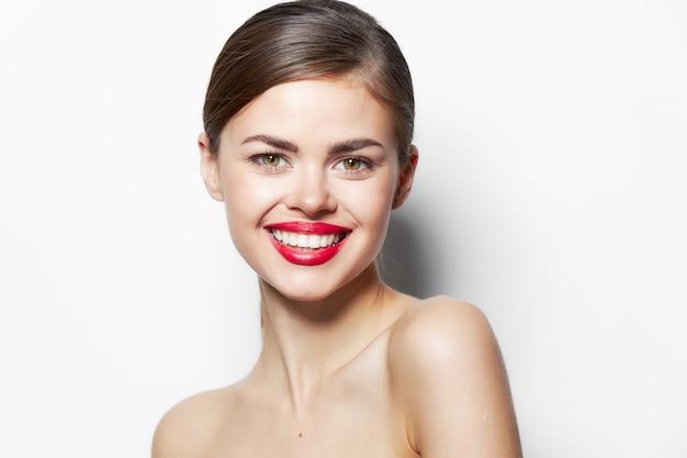 Jolie femme lèvres rouges sourire épaules dénudées peau claire