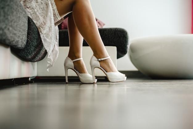 Jolie femme en lingerie enfile des talons hauts sur ses belles longues jambes.