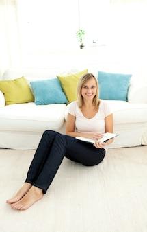 Jolie femme lisant un livre dans le salon