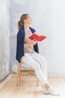 Jolie femme lisant un livre à la maison