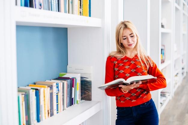 Jolie femme lisant près de la bibliothèque