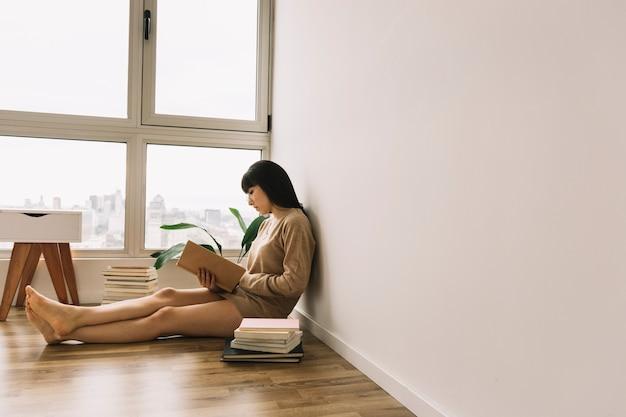 Jolie femme lisant sur le sol