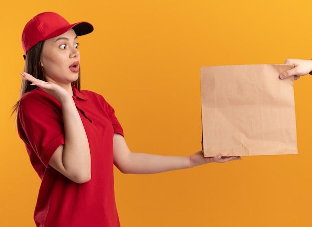 Jolie femme de livraison anxieuse en uniforme se tient avec la main levée et donne un paquet de papier à quelqu'un sur orange