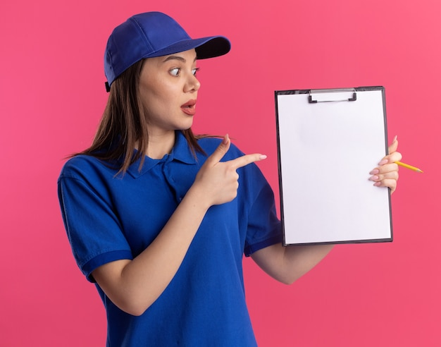 Jolie femme de livraison impressionnée en uniforme regarde et pointe le presse-papiers sur rose