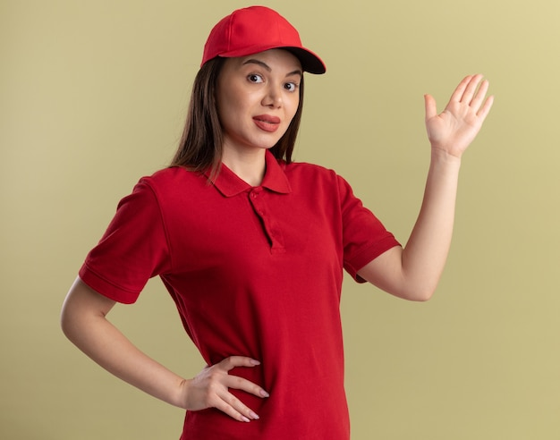 Jolie femme de livraison impressionnée en uniforme se dresse avec la main levée sur vert olive