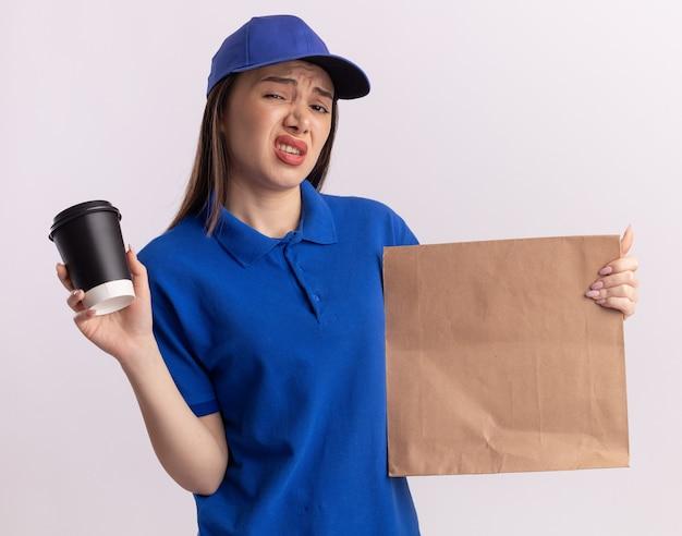 Jolie femme de livraison sans plaisir en uniforme détient un paquet de papier et une tasse de papier sur blanc
