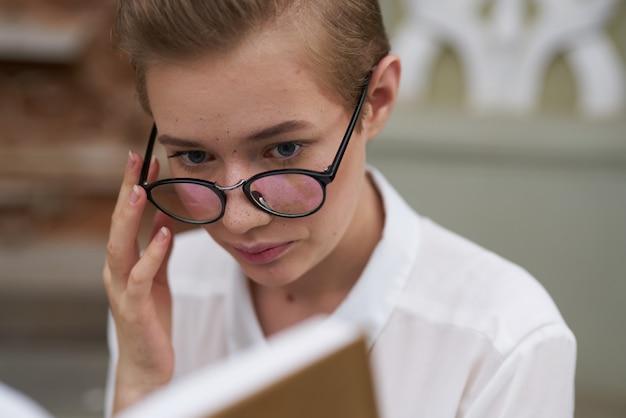Jolie femme avec un livre dans ses mains à l'extérieur de la communication de lecture