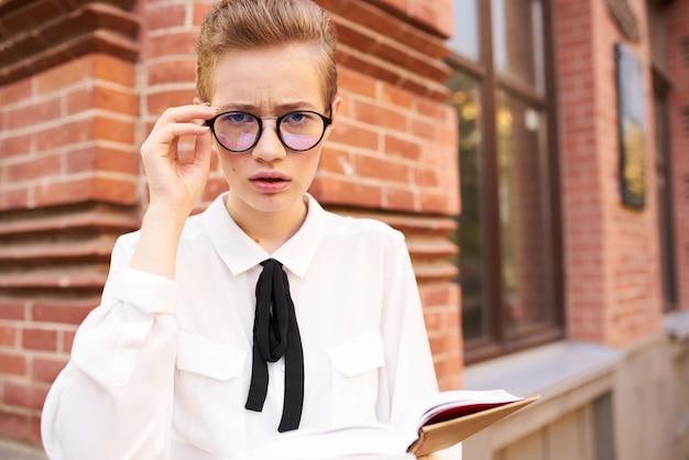 Jolie femme avec un livre dans ses mains à l'extérieur de l'éducation à la lecture