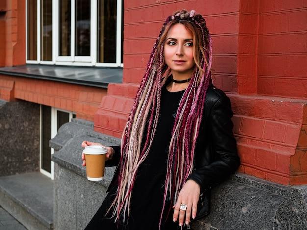 Jolie femme avec de longs dedreadlocks roses tient un café tourné avec un mur de briques