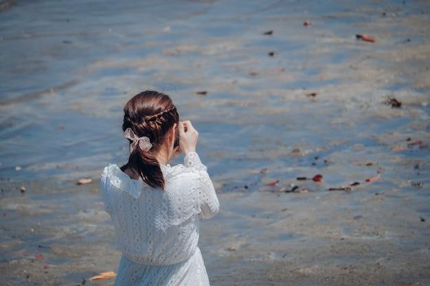 Jolie femme lumineuse, prenant des photos, le long de la plage le matin.