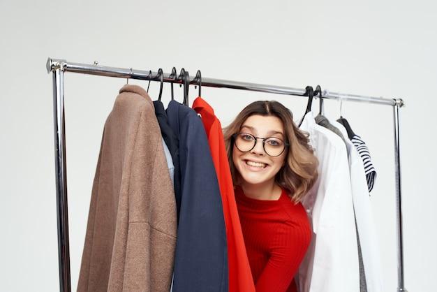 Jolie femme avec des lunettes à côté de vêtements mode fun fond clair. photo de haute qualité