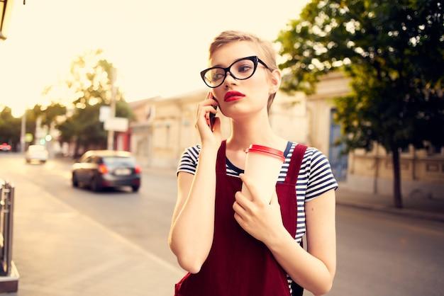 Jolie femme avec des lunettes dans la rue parlant au téléphone en été