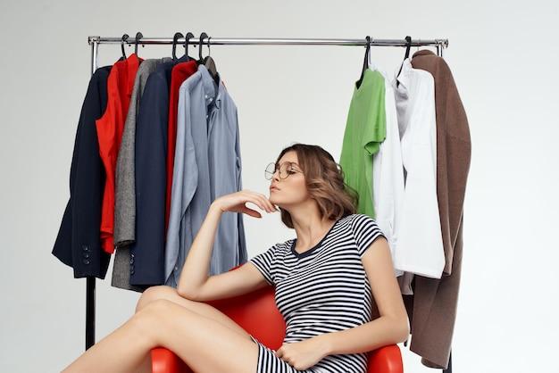 Jolie femme avec des lunettes essayant sur fond clair accro du shopping magasin de vêtements