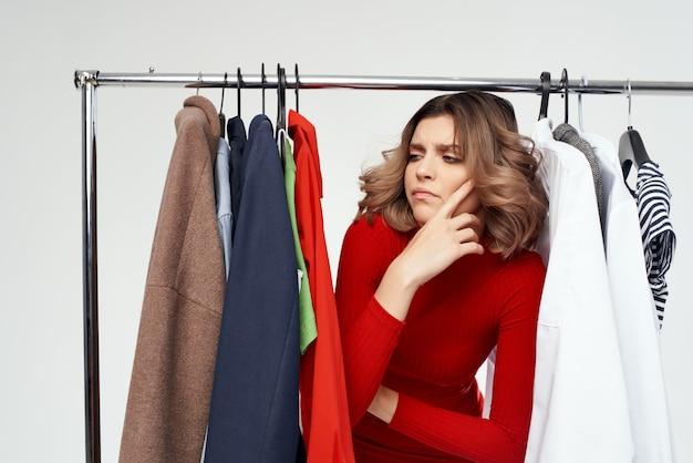 Jolie femme avec des lunettes essayant sur fond isolé shopaholic magasin de vêtements