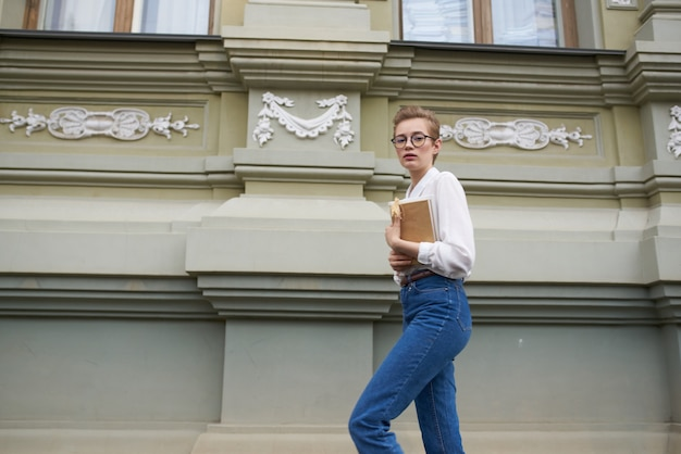 Jolie femme avec des lunettes se promenant dans la ville avec un livre mode de vie. photo de haute qualité