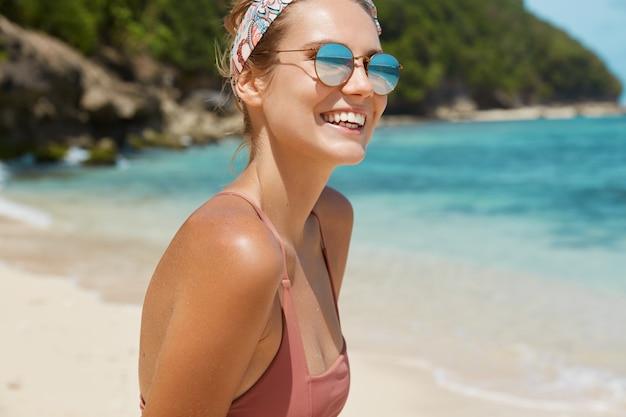 Jolie femme avec des lunettes de soleil et maillot de bain sur la plage