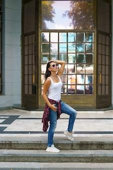 Jolie femme à lunettes de soleil pose sur les marches de la rue près du bâtiment en jeans et un tsh blanc...