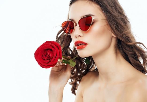 Jolie femme à lunettes de soleil avec une rose dans ses mains épaules nues