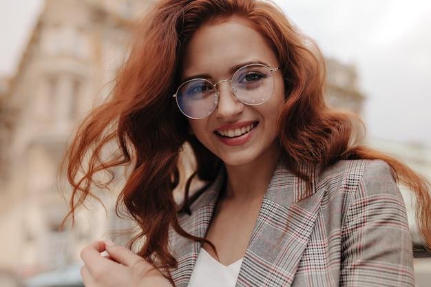Jolie femme à lunettes et veste regardant dans la caméra