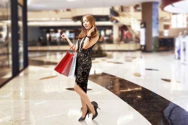 Jolie femme de luxe asiatique en robe noire, tenant les sacs
