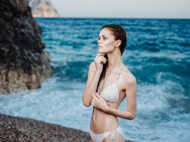 Jolie femme en maillot de bain blanc en se basant sur la mode loisirs des tropiques de la plage