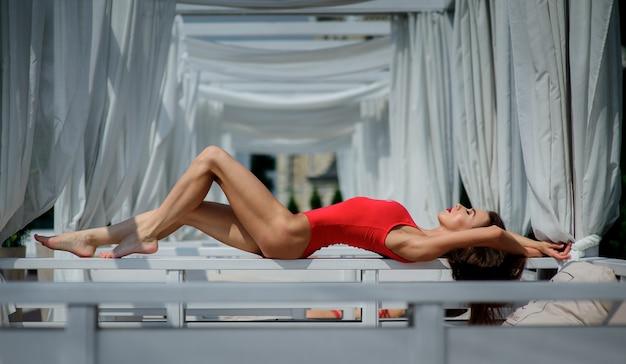 Jolie femme en maillot de bain rouge est assise sur un canapé blanc à l'extérieur