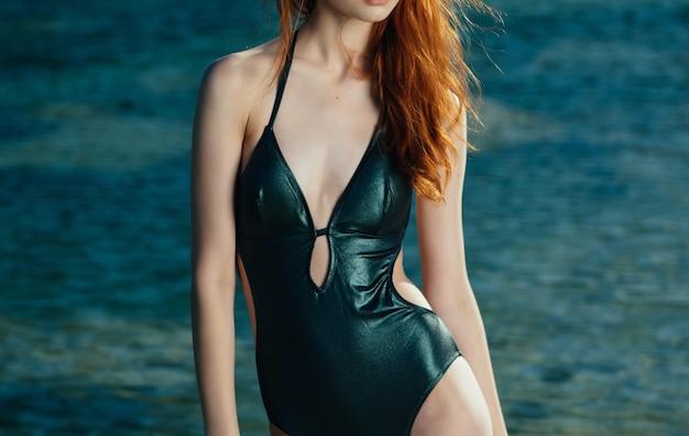 Jolie femme en maillot de bain vert lunettes de soleil de luxe paysage. photo de haute qualité