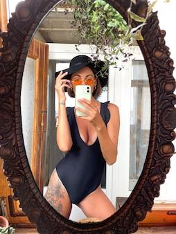 Une jolie femme à la maison prend un selfie photo dans un miroir sur un téléphone portable pour des histoires et des publications sur les réseaux sociaux, portant un maillot de bain d'été noir