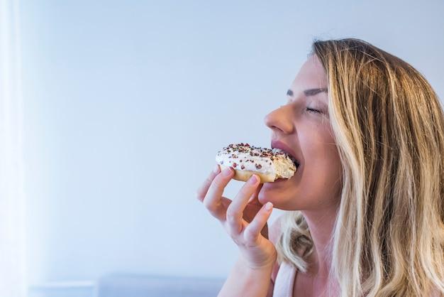 Jolie femme mange un beignet délicieux